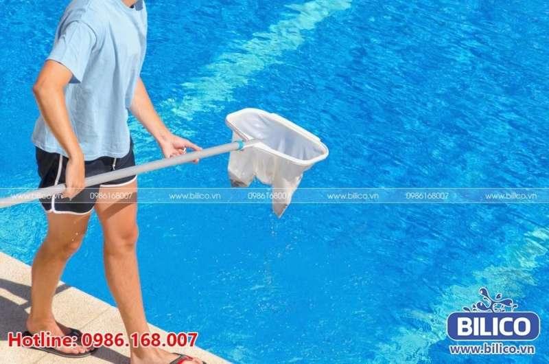 Sử dụng vợt vớt rác để hớt lá cây, rác tại hồ bơi